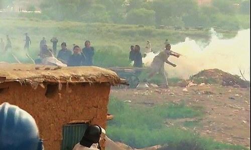 Slum-dwellers throwing stones at policemen. ─ DawnNews