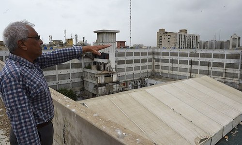 In this photograph taken on August 22, 2015, manager of the Metropole Hotel manager Imtiaz Moghal gestures from the roof of the now-closed hotel in Karachi. - AFP