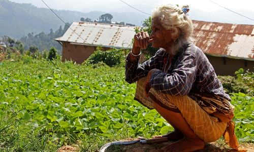 A woman affected by climate change in Nepal sits gloomily with her sickle. — Photo by author