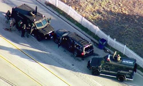 In this image taken from video, armored vehicles surround an SUV following a shootout in San Bernardino. -AP