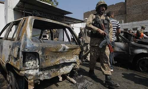A soldier walks past damaged vehicles. ─ AP