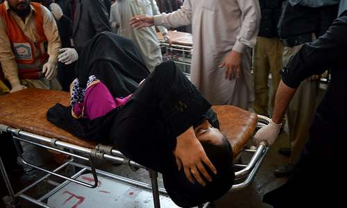 Volunteers rush an injured woman to a hospital in Peshawar. ─ AP