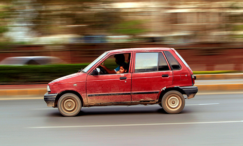 A girl looks out from a Suzuki Mehran as she travel along a road in Rawalpindi. ─ Reuters