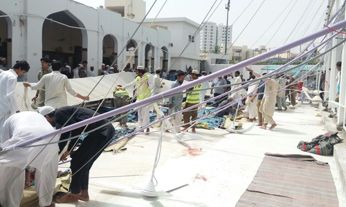 Rescue workers and worshippers attempt to move the debris after a roof collapsed. ─ DawnNews