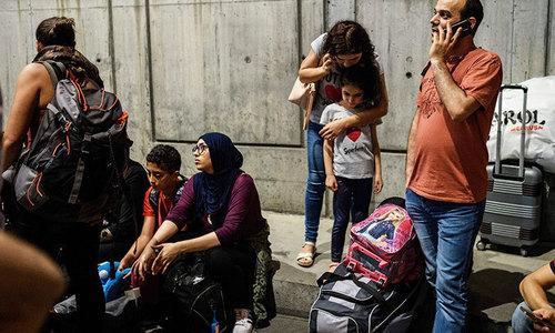 استبول کےکمال اتاترک انٹرنیشنل ایئرپورٹ پر دھماکوں کے بعد مسافر پریشان کھڑے ہیں—۔فوٹو/ اے ایف پی