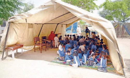 Students attend their class in a tent at Islamabad Model School for Girls, H-13. ─ File photo