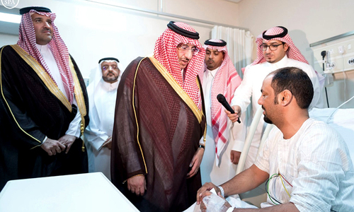 Saudi Crown Prince and Interior Minister Mohammed bin Nayef (centre) visits a wounded man who was injured after a suicide bomber detonated a device near the security headquarters of the Prophet's Mosque.  ─ Saudi Press Agency/Reuters
