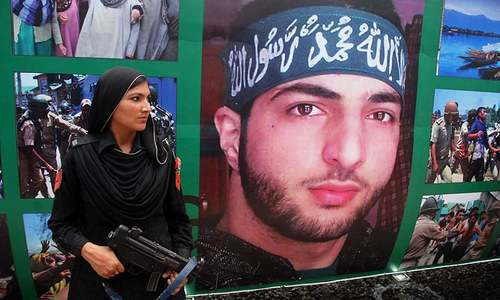 Police woman stands in front of a picture of Burhan Wani during inauguration ceremony of Azadi Train at Margalla Railway Station, Islamabad. ─ Online