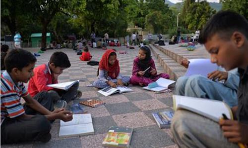 Pupils take part in a lesson at a makeshift school in a park in Islamabad.─AFP