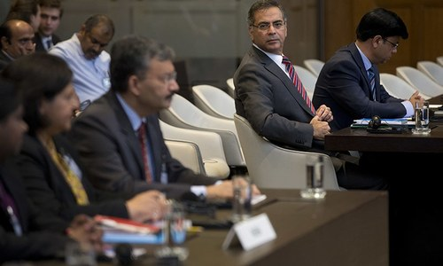 Moazzam Ahmad Khan and Dr Deepak Mittal wait for judges to enter and read the World Court's verdict. ─ AP