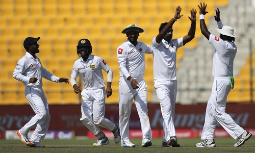 Sri Lanka's bowler Dilruwan Perera with teammates celebrate dismissal of Pakistan's Babar Azam during their fifth day at First Test cricket match, in Abu Dhabi on Monday, Oct. 2, 2017. —AP