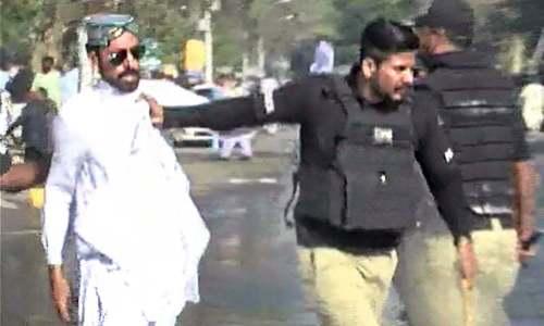 Police detain a protester in Karachi.— DawnNews