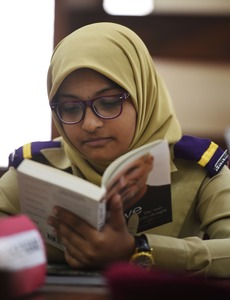 Affifa Alam, a cadet, reads a book in a library at the Pakistan Army's first Girls' Cadet College in Mardan. —AFP