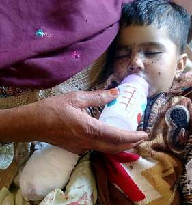 Seven-months-old Noor Fatima is being fed milk after initial treatment in DHQ Hospital Kotli. According to Medical Superintendent Dr Tariq Mehmood she lost four fingers of her right hand to Indian shelling. Her mother Sahiba Matloob, 23, is also being treated at the same hospital. —Photo by Author