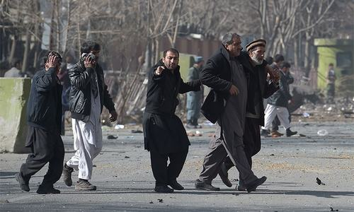 Afghan volunteers help an injured man at the scene of the car bombing.— AFP