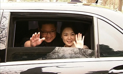 This video grab shows Kim Jong Un (L) and his wife Ri Sol Ju (R) waving goodbye as they depart by car following a meeting with China's President Xi Jinping in Beijing this week. — AFP/CCTV
