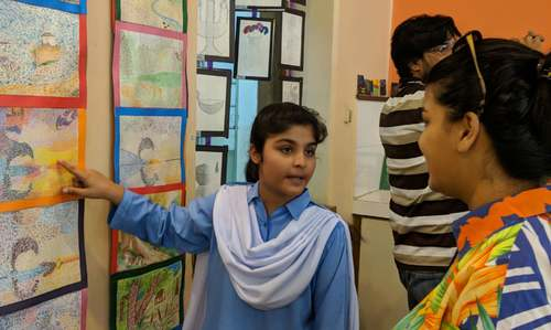 A student explaining the artwork to visitors.