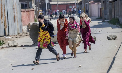 Kashmiri girls run for cover as Kashmiri youth clash with Indian paramilitary soldiers during a protest against the killing of rebels in Srinagar. — AP