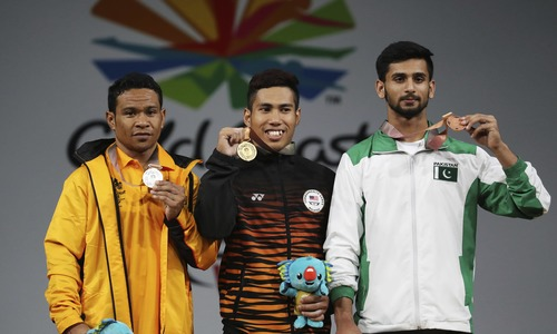 Malaysia's Men's 62kg weightlifting gold medallist Muhamad Aznil Bidin, centre, stands with Papua New Guinea's silver medallist More Baru, left, and Pakistan's bronze medallist Talha Talib, during the medal ceremony of the Commonwealth Games in Gold Coast, Australia, Thursday, April 5, 2018. — AP