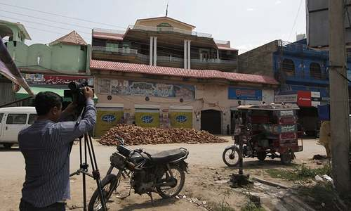 A member of the media films the house of Sana Cheema in the neighbourhood of Mangowal, near Gujrat. — AP