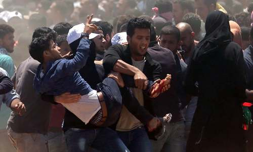 Palestinians carry a demonstrator injured during clashes with Israeli forces. — AFP