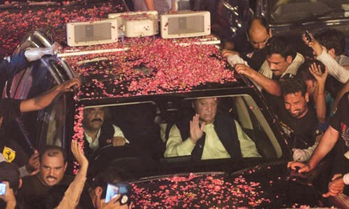 Nawaz Sharif waves as his convoy passes through supporters at a rally on August 12, 2017 in  Lahore | AFP