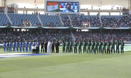 Members of Indian, left, and Pakistani teams stand as the national anthems of their countries are played. — AP