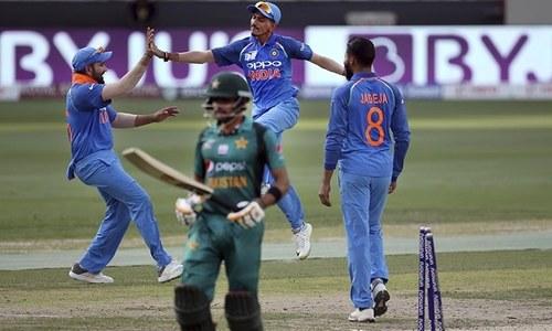 Sharma, left, celebrates with teammates the dismissal of Pakistan's Babar Azam, front. — AP