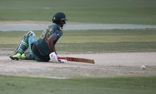 Fakhar Zaman falls on the ground after he was dismissed by India's Kuldeep Yadav. — AP