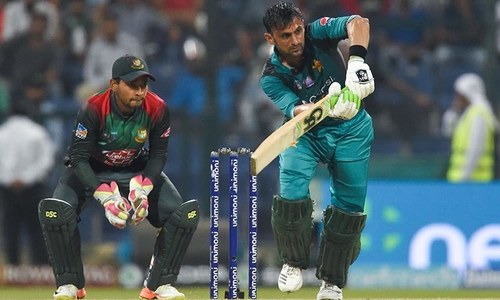 Shoaib Malik (R) plays a shot as Bangladesh wicketkeeper Mushfiqur Rahim (L) looks on — AFP