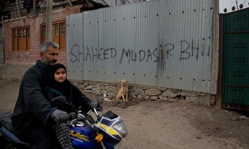 In this Dec 26, 2018 photo, a Kashmiri man along with his daughter drives past a graffiti on the house of Mudassir Rashid Parray, referring to him as a martyr, in Hajin village, north of Srinagar.
