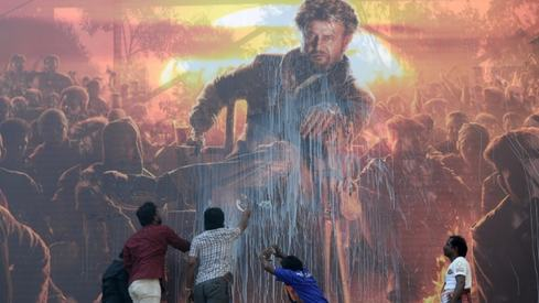 Indian film buffs are stealing milk and pouring it on movie posters for good luck