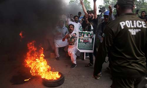 Supporters of Maryam Nawaz chant slogans and burn tires before her appearance for the court proceedings. — Reuters