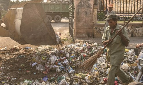 Protesting workers dump garbage in front of KMC building in Karachi