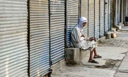 An elderly man sits at a shuttered market during a countrywide strike against a hike in prices on July 13. — AFP/File