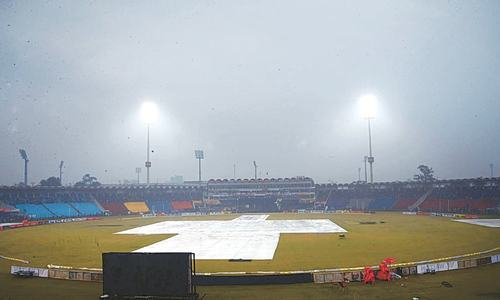 LAHORE: Ground staff cover the pitch during rain showers before the start of the third T20 between Pakistan and Bangladesh at the Gaddafi Stadium on Monday.—Online