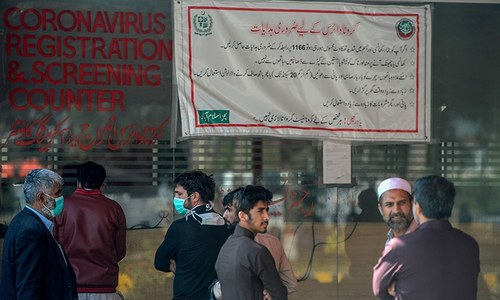 Residents wearing facemasks as a preventive measure against the COVID-19 coronavirus, wait for their turn at a coronavirus registration and screening counter at the Pakistan Institute of Medical Sciences Hospital in Islamabad on March 19, 2020. — AFP