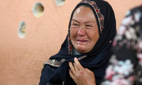 An Afghan woman cries while looking at family members at the hospital. — Reuters