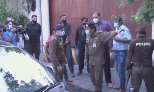 Police officials gather outside Shehbaz Sharif's Lahore residence after he misses NAB hearing