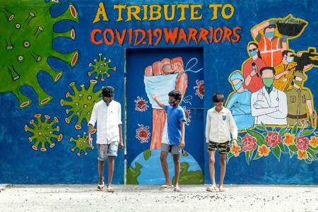 A youth gestures as he walks with others past a mural dedicated to frontline workers fighting against the spread of the coronavirus in Chennai on August 6, 2020. — AFP