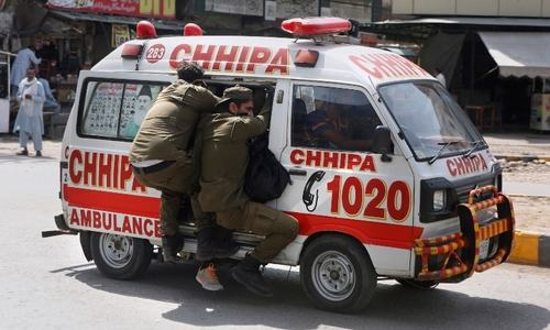 Police officers hang on to an ambulance carrying their colleagues who were injured during a clash with TLP supporters in Lahore, Sunday. — AP