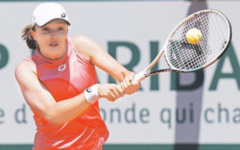 POLAND'S Iga Swiatek hits a return to Maria Sakkari of Greece during their French Open quarter-final on Wednesday.—AP