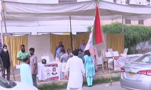 Workers gather at an MQM election camp during polling in Karachi. — DawnNewsTV