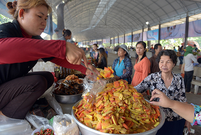 A Cambodian vendor (L) packages food for a customer at a tourist site on the outskirts of Phnom Penh. Cambodia's economic growth accelerated to 7.3 percent in 2012 thanks to buoyant activity in the agricultural, tourism, construction and garment sectors, Prime Minister Hun Sen said.—Photo by AFP