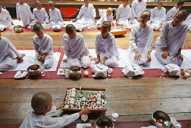 Doughnuts are served with other food as novice nuns have their lunch at the Sathira-Dhammasathan Buddhist meditation centre in Bangkok. A group of Thai girls are choosing to spend part of their school holidays as Buddhist nuns, down to having their heads shaven at the meditation centre. The centre, founded in 1987, is a learning community for peace and harmony that has programs open to people regardless of age and gender.—Photo by Reuters