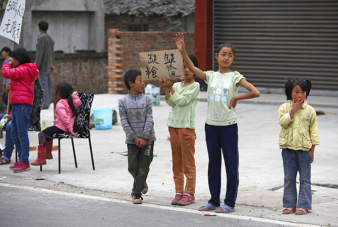 "Children on the roadside hold a sign that reads ""no food, no tent"" after a strong 6.6 magnitude earthquake hit the remote, mostly rural and mountainous Lushan county, Sichuan province. Rescuers struggled to reach a remote corner of southwestern China on Sunday as the toll of the dead and missing from the country's worst earthquake in three years climbed to 203 with more than 11,000 injured. The 6.6 magnitude quake struck in Lushan county, near the city of Ya'an in the southwestern province of Sichuan, close to wher"