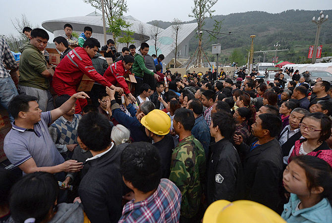 Rescue workers (top L) distribute food after a magnitude 7.0 earthquake hit Lushan, Sichuan Province. At least 160 people were killed and 6,700 injured when a strong earthquake hit a mountainous part of southwestern China on April 20, destroying thousands of homes and triggering landslides.—Photo by AFP