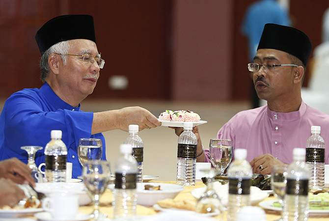 Malaysia's Prime Minister Najib Razak (L) passes a plate of food to opponent Fariz Musa of the People's Justice Party after submitting their nomination papers to contest in Pekan constituency for the upcoming general elections in Pekan, 300 km east of Kuala Lumpur. Malaysia will hold general elections on May 5 in what could be the toughest test of his ruling coalition's 56-year grip on power in Southeast Asia's third-largest economy.—Photo by Reuters