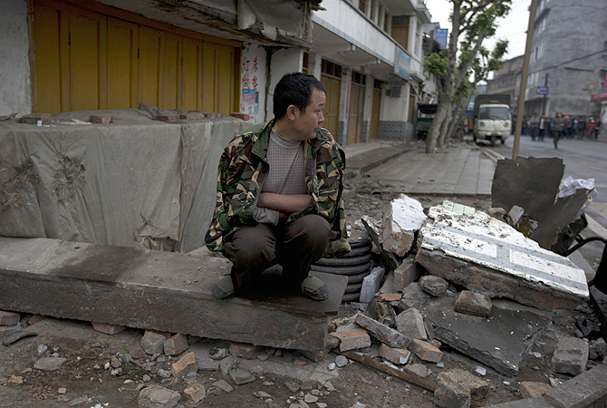 A man sits on a piece of rubble while waiting for food to be distributed in the quake hit county of Lushan in southwestern China's Sichuan province. Saturday's earthquake in Sichuan province killed at least 186 people, injured more than 11,000 and left nearly two dozen missing, mostly in the rural communities around Ya'an city, along the same seismic fault where a devastating quake to the north killed more than 90,000 people in Sichuan and neighboring areas five years ago in one of China's worst natural disasters.—
