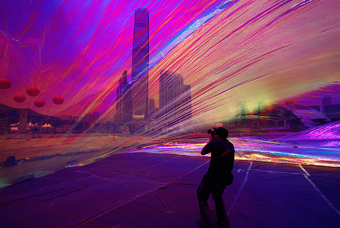 """A photographer takes picture from inside an art piece """"Poetic Cosmos of the Breath"""" by Argentina-born artist Tomas Saraceno as part of an exhibition """"Inflation!"""" at the site of an upcoming park in the West Kowloon cultural district in Hong Kong April 24, 2013. """"The Park"""" as it will be called, will cover 14 hectares of landscaped public space devoted to the arts and culture and will open by phases starting from 2014/15, according to the official press release. — Reuters Photo"""